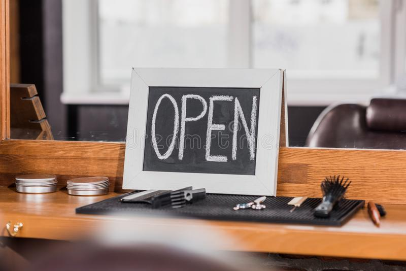 Blackboard with open sign leaning on mirror at barbershop with tools on rubber mat. And on counter royalty free stock photo
