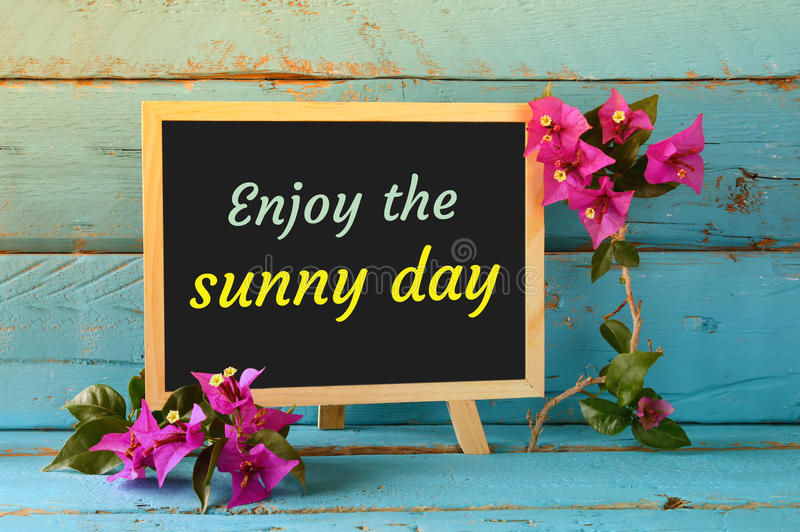 Blackboard over blue wooden shelf with the phrase ENJOY THE SUNNY DAY. royalty free stock image