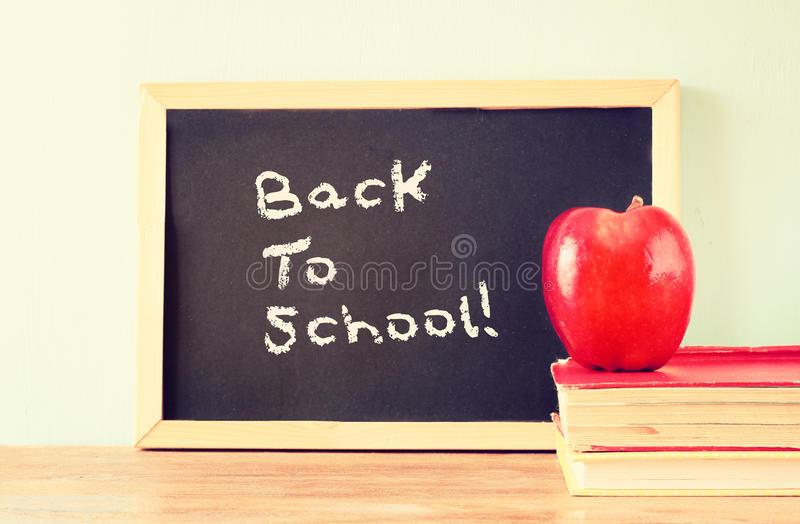 Blackboard with the phrase back to school, apple and stack of books. filtered image royalty free stock images