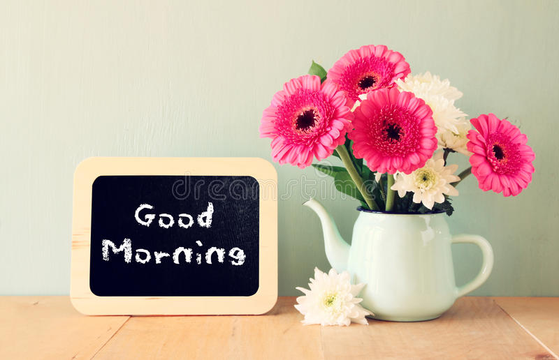 Blackboard with the phrase good morning written on it next to vase with fresh flowers stock photo