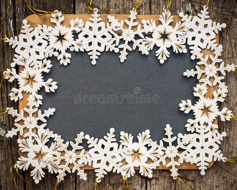 Blackboard puste miejsce obramiający w drewnianych płatkach śniegu obraz stock