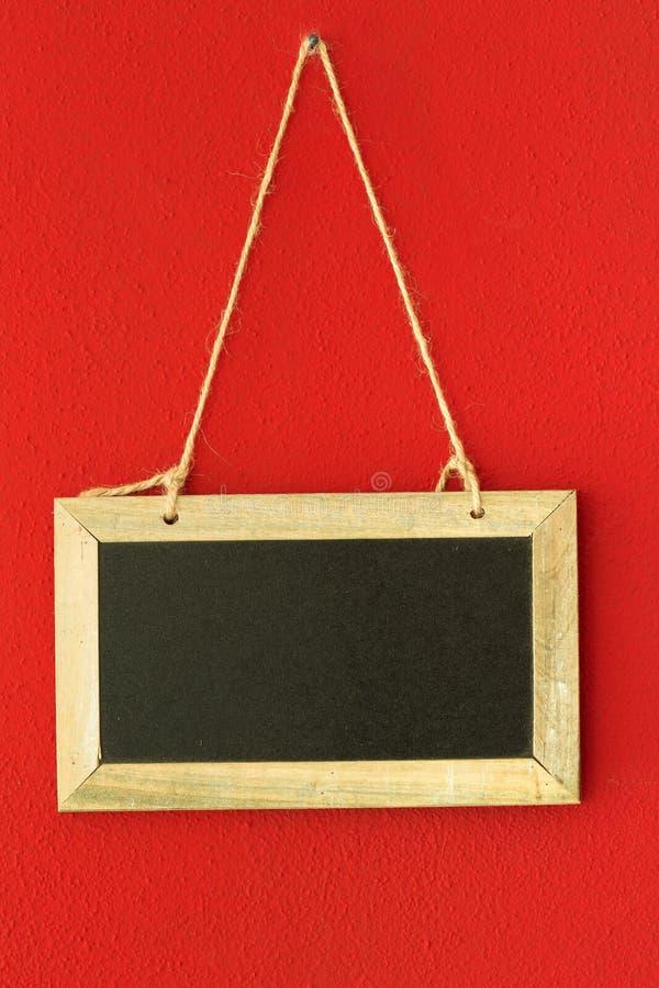 Blackboard on red wall stock image
