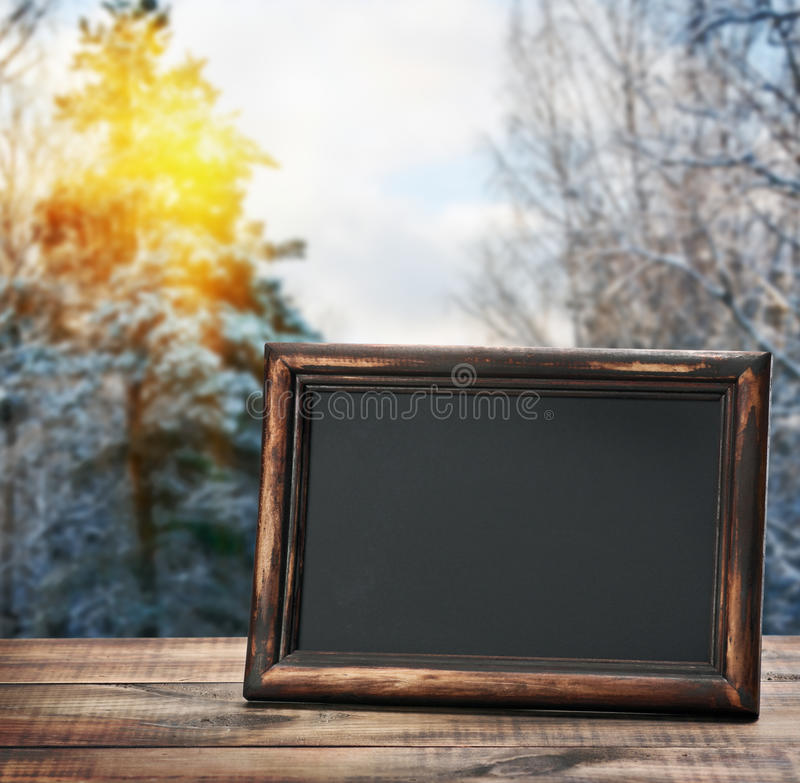Blackboard on the table. Against the background of the winter forest stock photo