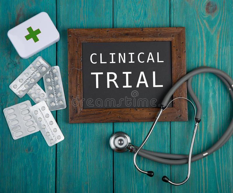 Blackboard with text & x22;Clinical trial& x22;, pills and stethoscope on blue wooden background royalty free stock images