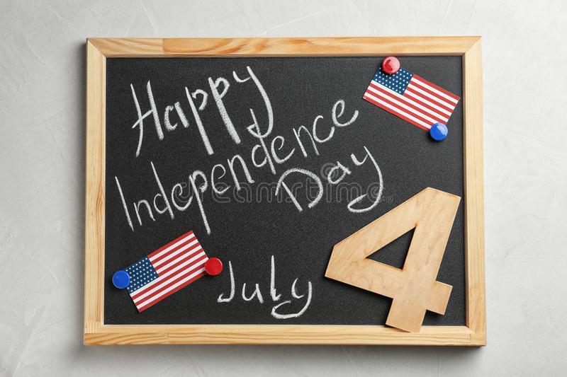 Blackboard with text Happy Independence Day, wooden number and USA flags stock photos