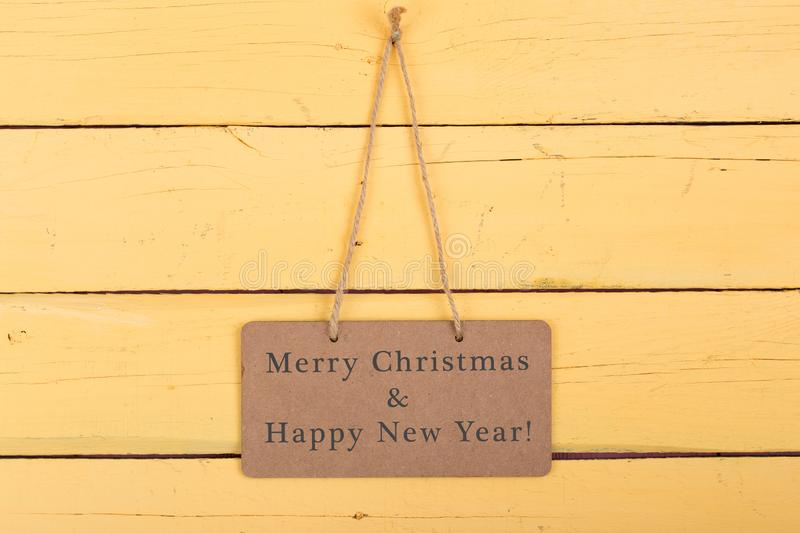 """Blackboard with text """"Merry Christmas & Happy new year. """" on yellow wooden background stock photos"""