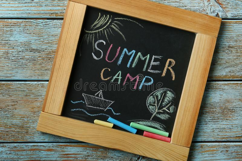 Blackboard with text SUMMER CAMP, drawings and chalk sticks on wooden background stock photography