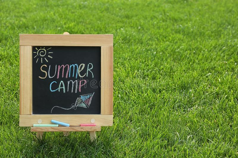 Blackboard with text SUMMER CAMP and drawings on green grass. Space for stock images