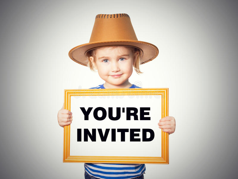 Blackboard. Text YOU'RE INVITED. Little Funny girl in striped shirt with blackboard. Text YOU'RE INVITED. Isolated on gray background royalty free stock photo