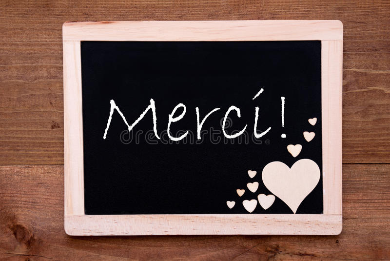 Blackboard With Wooden Hearts, Text Merci Means Thank You. Blackboard With French Text Merci Means Thank You. Brown Wooden Hearts. Wooden Background With Vintage royalty free stock image