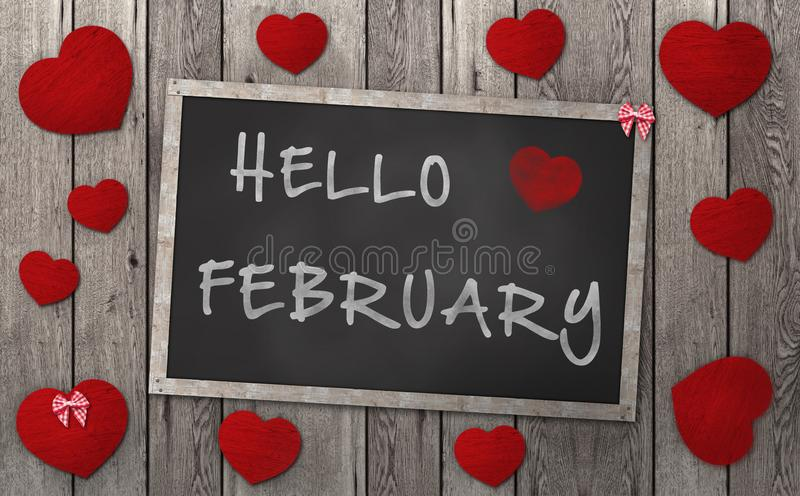 Blackboard with words hello february, surrounded by red hearts on weathered wooden background royalty free stock image