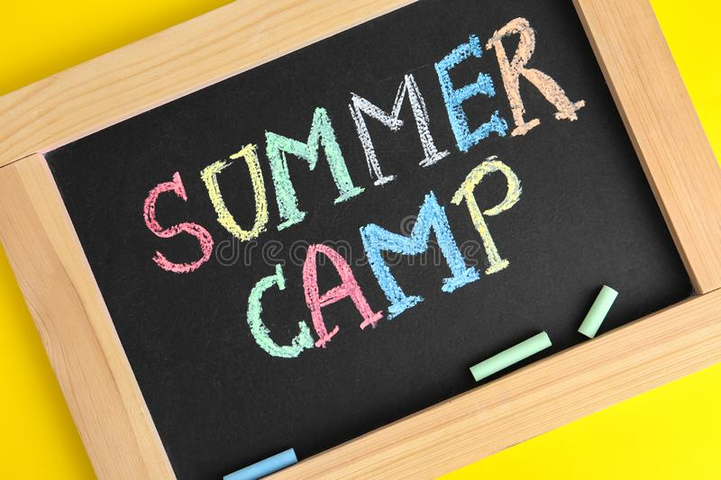 Blackboard with words SUMMER CAMP and colorful chalk on yellow background. Closeup royalty free stock photography