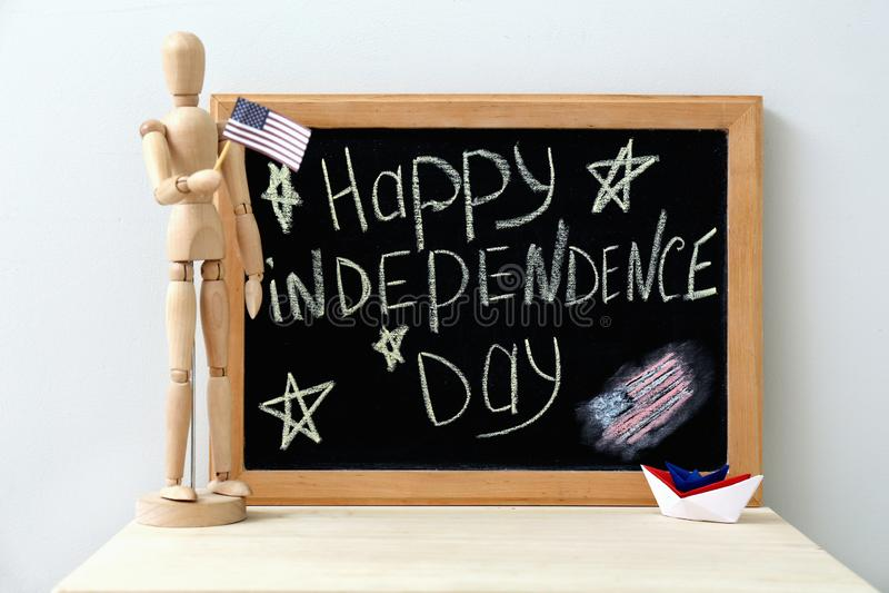 Blackboard z teksta SZCZĘŚLIWYM dniem niepodległości i drewniany mannequin z Amerykańską flagą państowową na światło stole zdjęcie stock