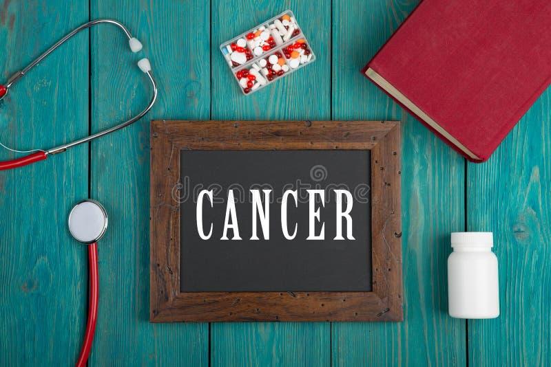 Blackboard z tekstem & x22; Cancer& x22; , książka, pigułki i stetoskop na błękitnym drewnianym tle, obraz stock