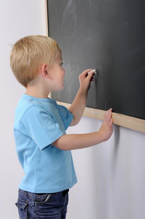 blackboardpojke little writing royaltyfri bild