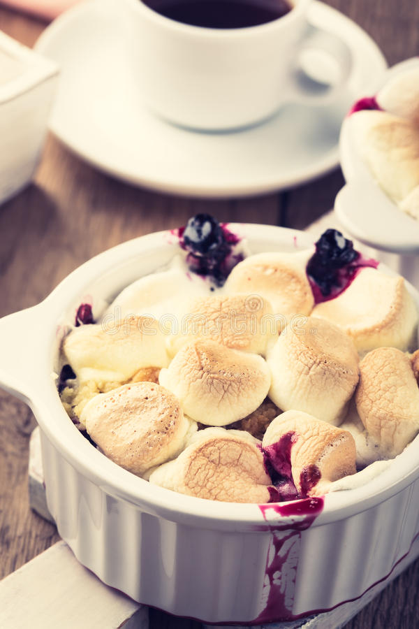 Blackcurrant apple crumble pie with marshmallow on top in ramek. Homemade blackcurrant apple crumble pie with marshmallow on top in ramekin on rustic table stock photos