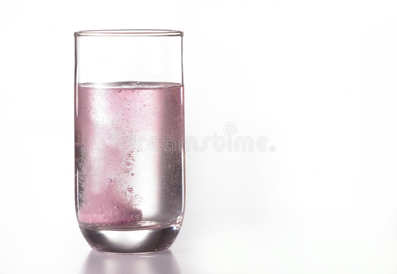 Blackcurrant effervescent tablet. Dissolving in a glass of water royalty free stock photos