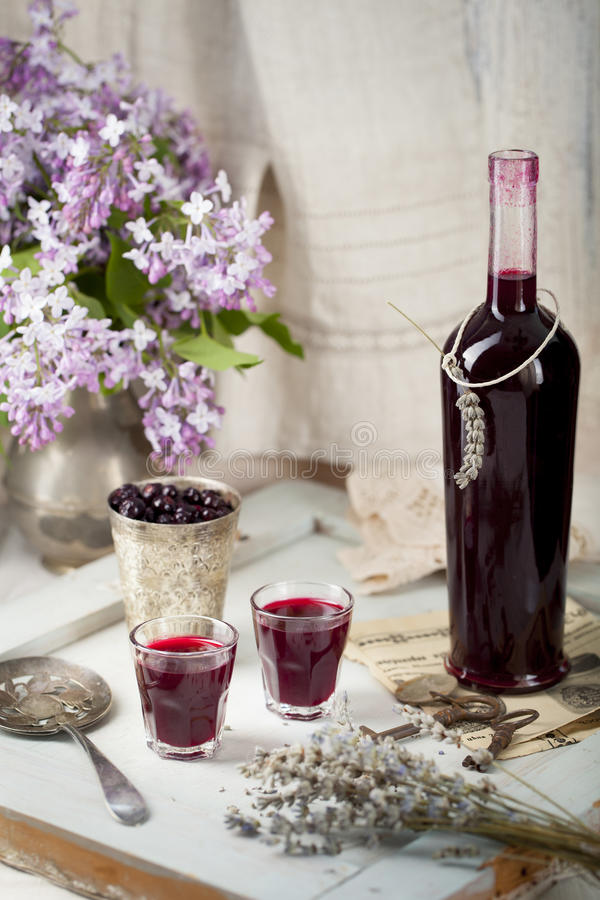 Blackcurrant homemade liquor with lilac flowers. Wooden background stock image