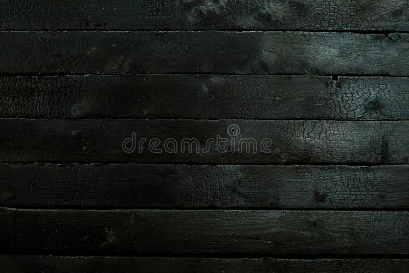 Blacked charred wood panel background texture. Burned in a fire for BBQ concepts in a full frame view stock photos