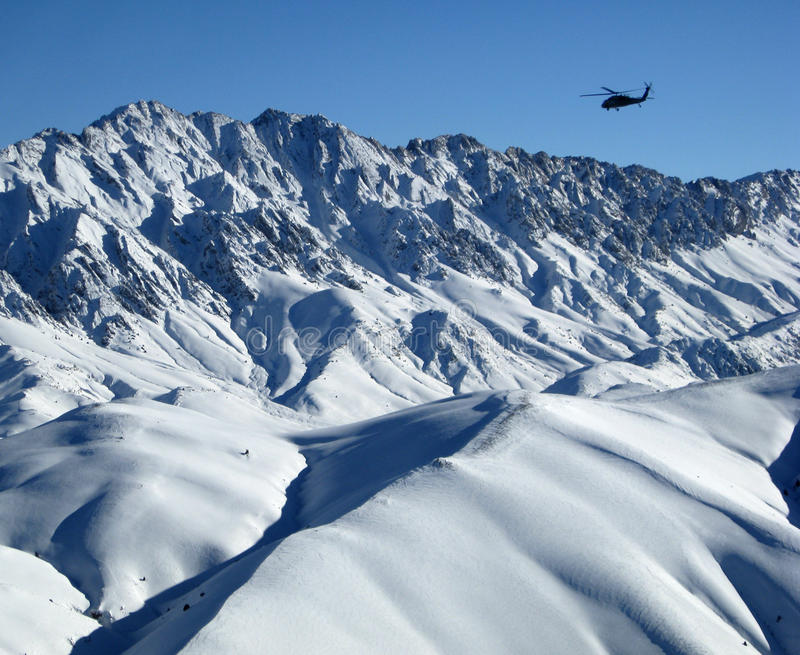 Blackhawk over snowy Afghanistan Mountains royalty free stock images