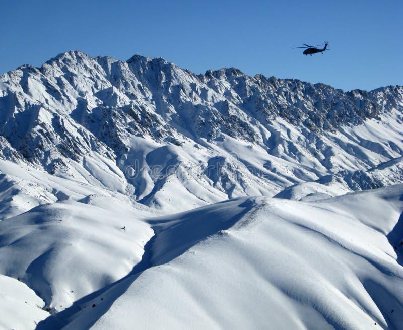 Blackhawk sopra le montagne nevose dell'Afghanistan immagini stock libere da diritti