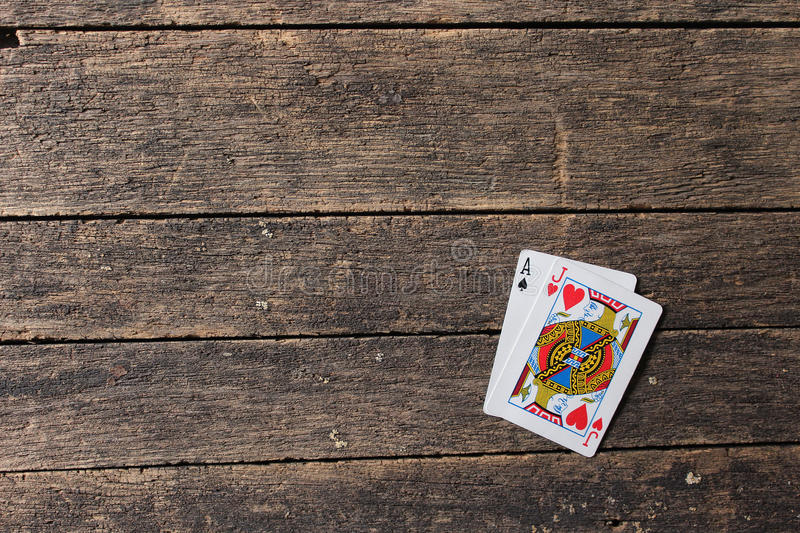 Blackjack Cards. The ace of spades and the Jack of hearts equals twenty-one in the game of Blackjack on a weathered table royalty free stock photo