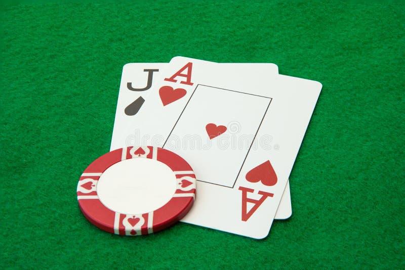 Blackjackhand mit Kasinochip auf grüner Tabelle lizenzfreie stockbilder