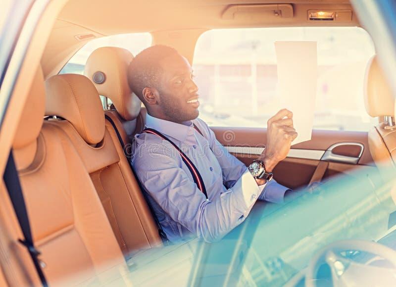 Blackman in een blauw overhemd zit op auto` s achterbank royalty-vrije stock afbeelding