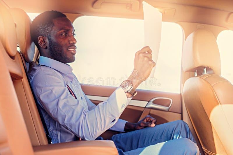 Blackman in een blauw overhemd zit op auto` s achterbank royalty-vrije stock foto's