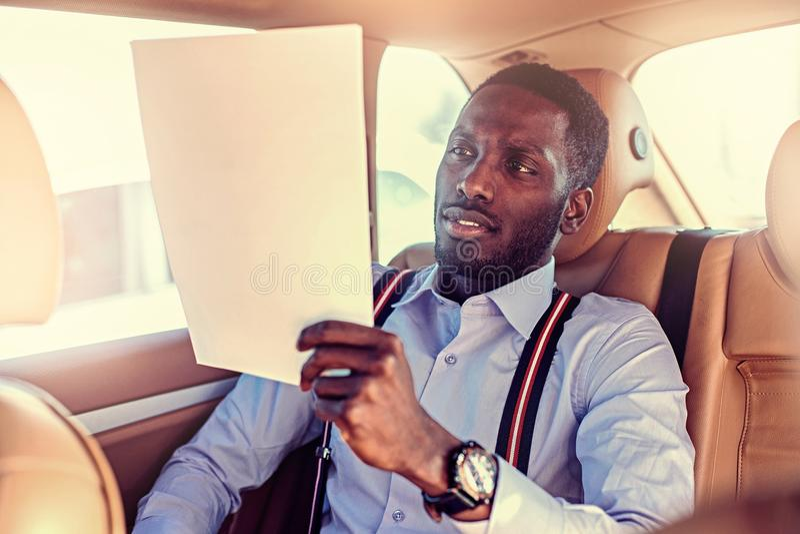 Blackman in een blauw overhemd zit op auto` s achterbank stock foto