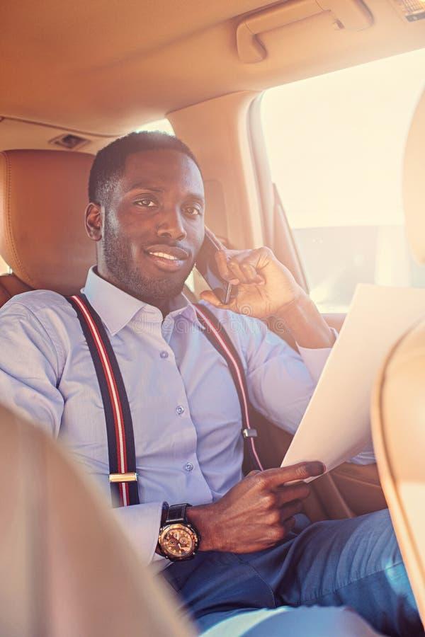Blackman in een blauw overhemd zit op auto` s achterbank stock fotografie
