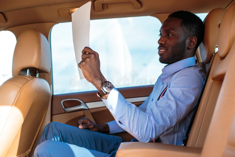 Blackman in una camicia blu si siede sul sedile posteriore del ` s dell'automobile immagine stock libera da diritti