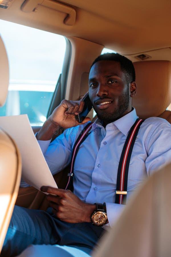Blackman in una camicia blu si siede sul sedile posteriore del ` s dell'automobile fotografie stock libere da diritti