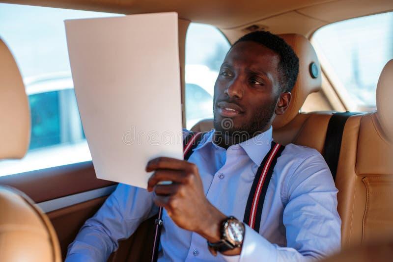 Blackman in una camicia blu si siede sul sedile posteriore del ` s dell'automobile immagini stock libere da diritti