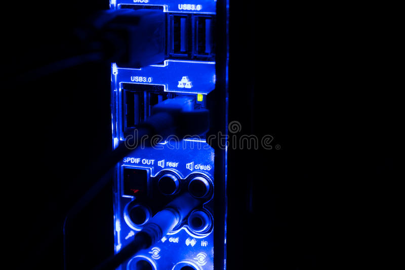 Blackout, blurred borders. Close up of blue network cables connected to black switch glowing in the dark royalty free stock photo