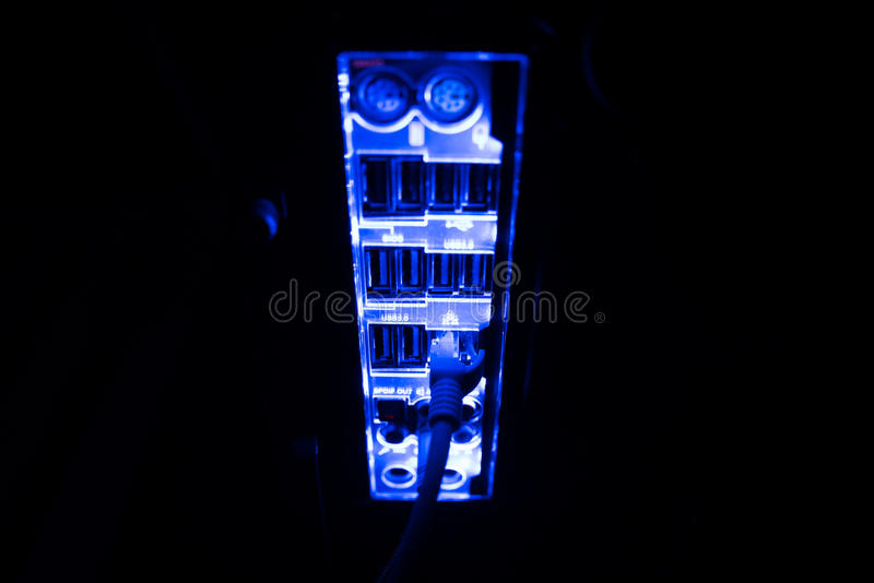 Blackout, blurred borders. Close up of blue network cables connected to black switch glowing in the dark royalty free stock photography