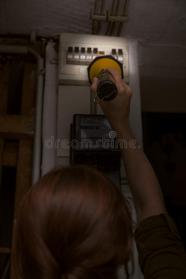 Blackout, electricity cut, woman with flashlight checking the br. Eaker box, fuse box royalty free stock photography
