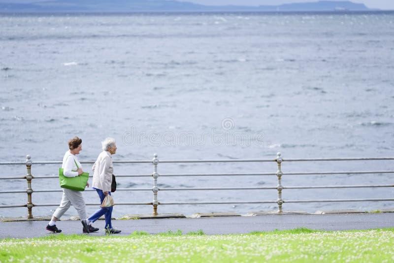 Blackpool, Angleterre/R-U - 6 juillet 2019 : Vieux couples supérieurs marchant au chemin de côte photos stock