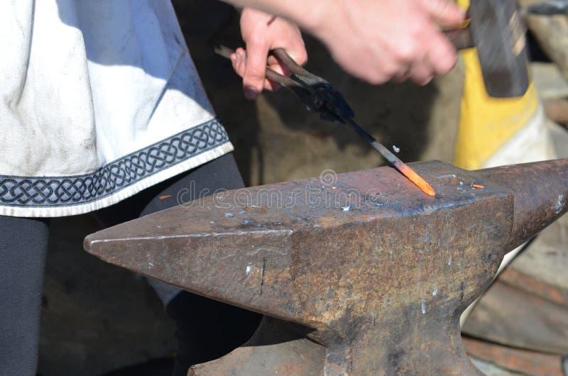 Blacksmith бьет краснокалильный утюг молотком на наковальне стоковые изображения rf
