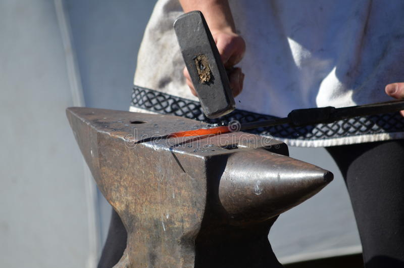 Blacksmith бьет краснокалильный утюг молотком на наковальне стоковое изображение