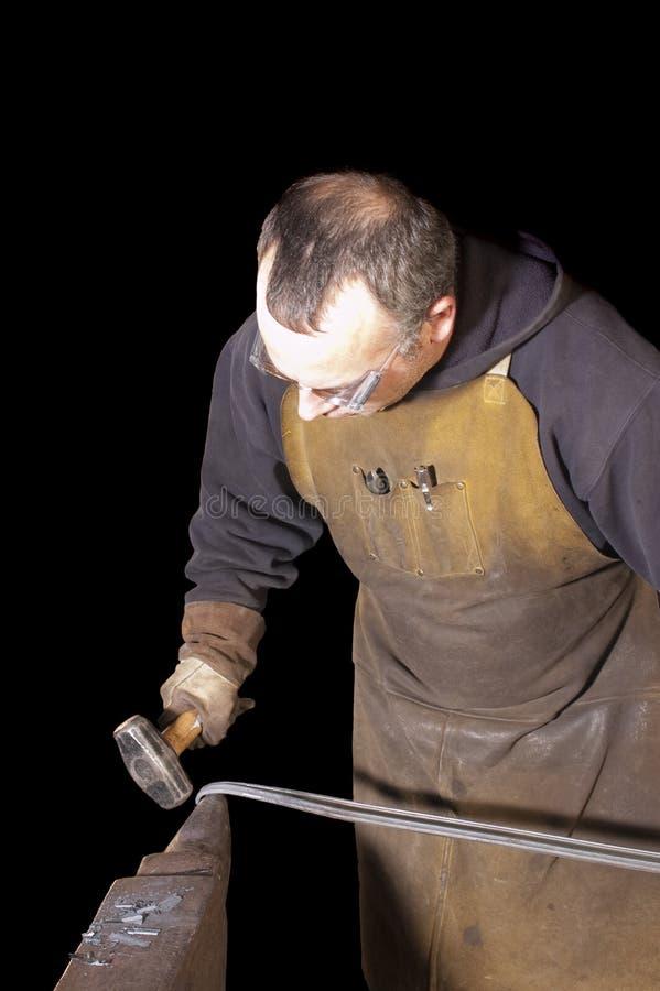 Blacksmith работая на декоративном поручне стоковые фото