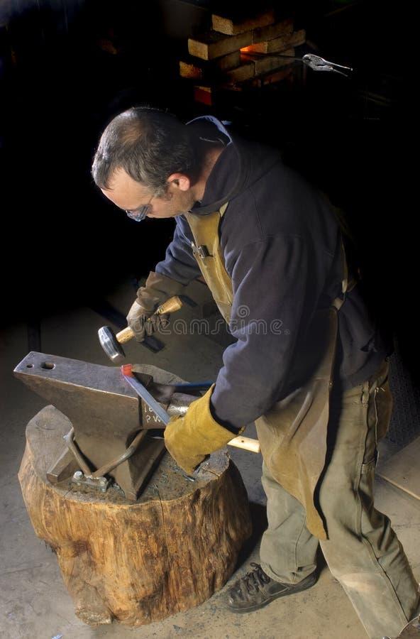 Blacksmith работая на декоративном поручне стоковое изображение