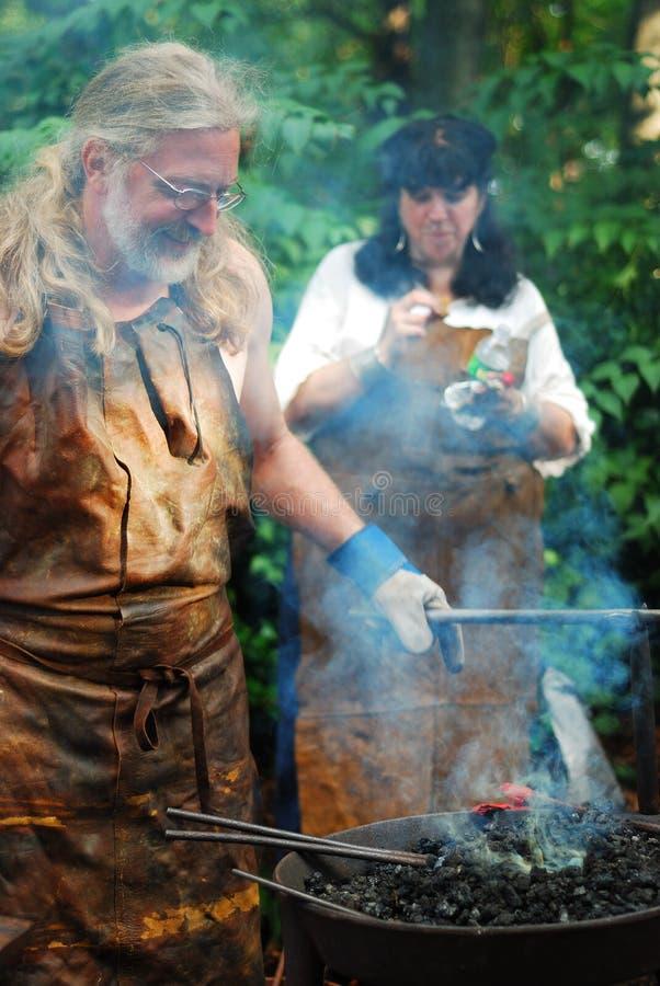 blacksmith строя средневековую шпагу стоковые изображения rf