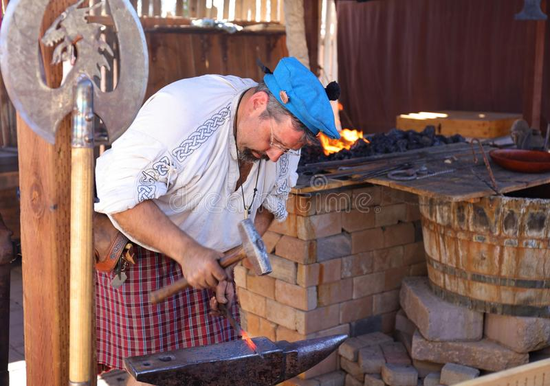 A Blacksmith Dressed in Traditional Outfit Forges Red Hot Metal into Swords stock photo
