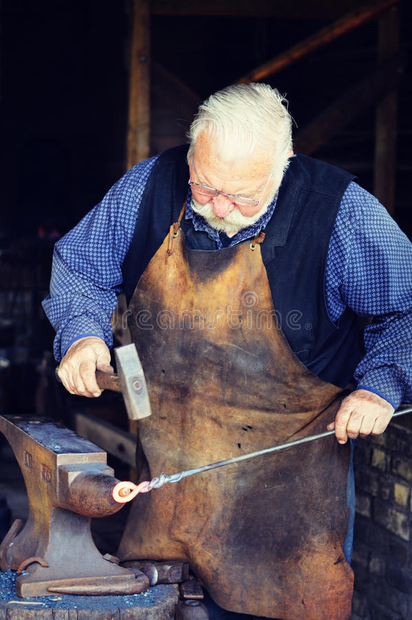 Blacksmith. An elderly blacksmith working in a blacksmith shop hammering at some hot iron