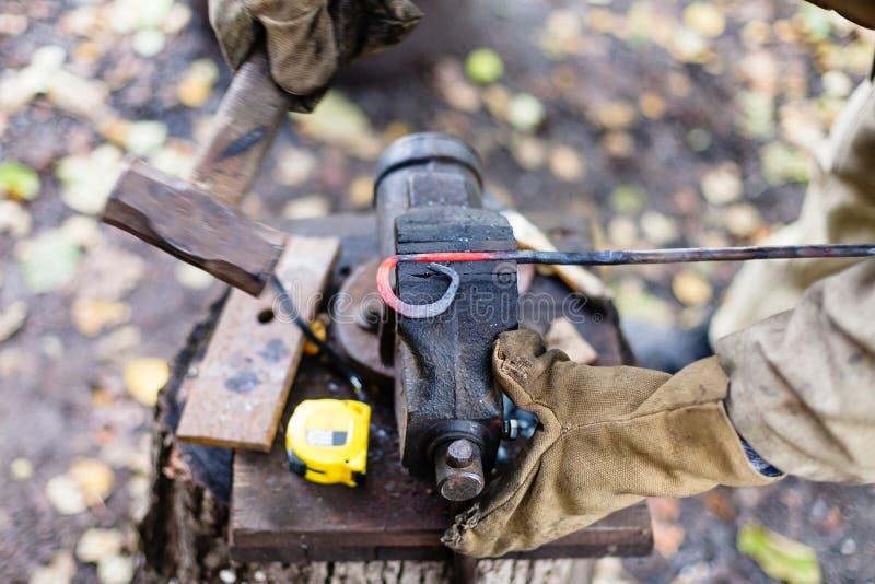 Blacksmith fałszuje gorącego czerwonego żelaznego prącie w imadle zdjęcie royalty free
