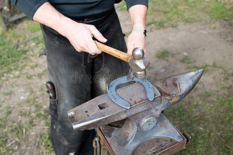 Blacksmith forges horseshoe with hammer on anvil. Ancient craft. Village craft. Blacksmith working metal. Tools for royalty free stock photo