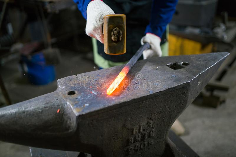 The blacksmith forges the luminous metal in the furnace, kicks out the sparks royalty free stock photography