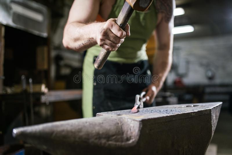 The blacksmith forges the luminous metal in the furnace, kicks out the sparks royalty free stock image