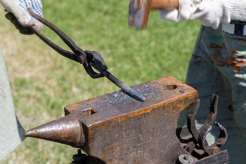 Blacksmith forges metal billet on the anvil against the background of green grass stock photography